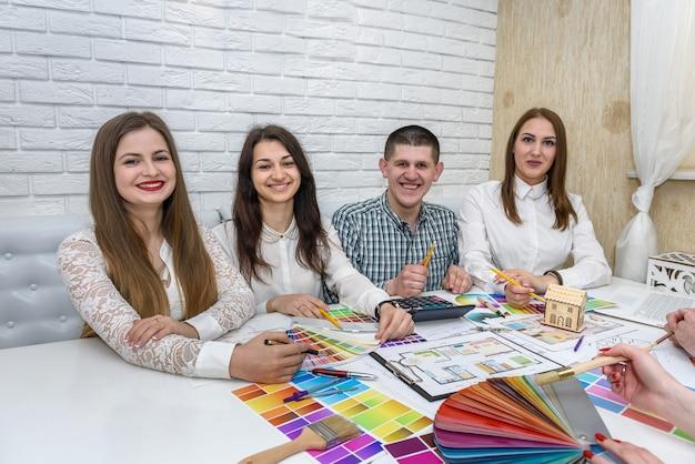 Grupa kreatywnych projektantów pracujących w biurze z paletami kolorów