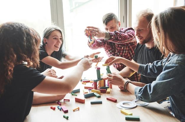 Grupa kreatywnych przyjaciół siedzi na drewnianym stole. ludzie bawili się podczas gry planszowej.
