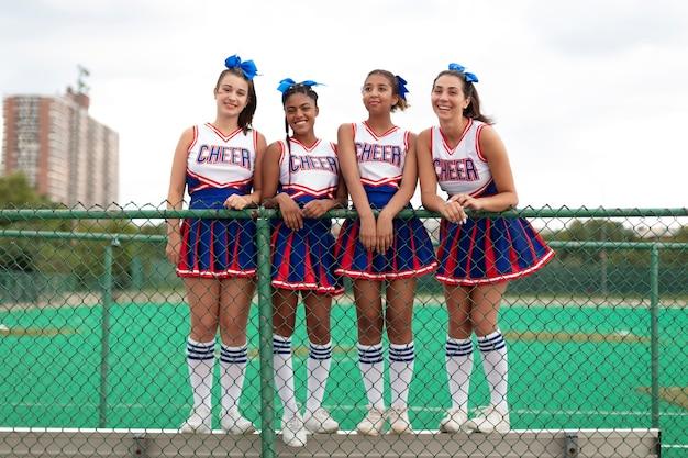 Grupa ładnych nastolatek cheerleaderek w uroczych mundurach