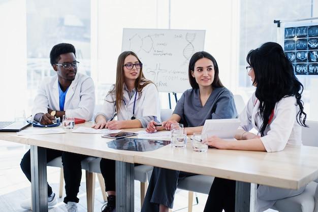 Grupa lekarzy bada historię choroby pacjenta. zespół wieloetnicznych młodych lekarzy o spotkaniu w sali konferencyjnej w nowoczesnym jasnym szpitalu.