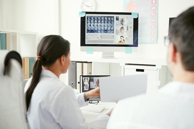 Grupa lekarzy na monitorze komputera omawiających zdjęcia rentgenowskie z kolegami podczas konferencji online