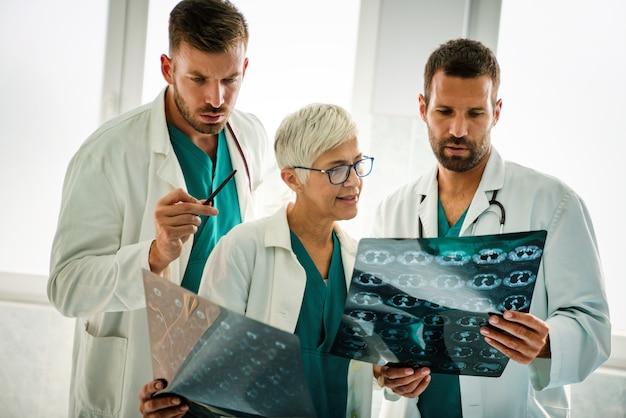Grupa lekarzy omawiająca diagnozę pacjenta patrzącego na zdjęcia rentgenowskie w szpitalu