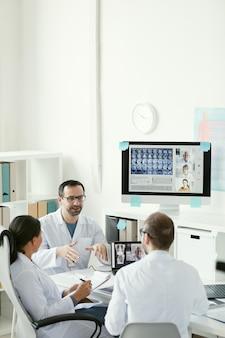 Grupa lekarzy pracujących w zespole podczas spotkania w biurze siedzą przy stole i omawiając zdjęcia rentgenowskie