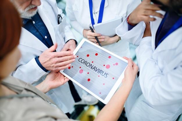 Grupa lekarzy rozmawiająca o koronawirusie na konferencji, brzuch.