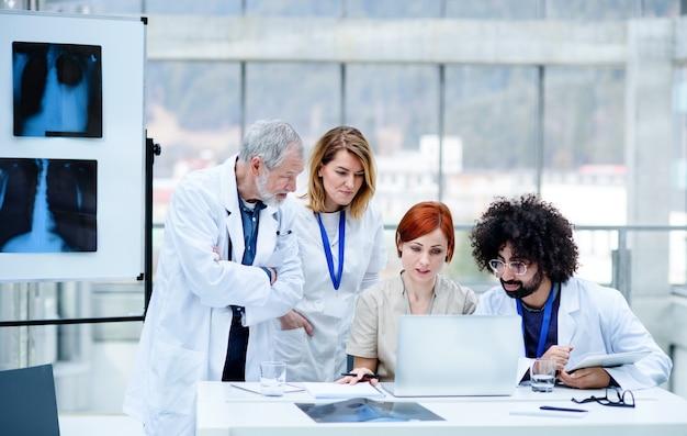 Grupa lekarzy rozmawiających o koronawirusie na konferencji.