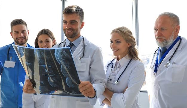 Grupa lekarzy sprawdzających zdjęcia rentgenowskie w szpitalu.