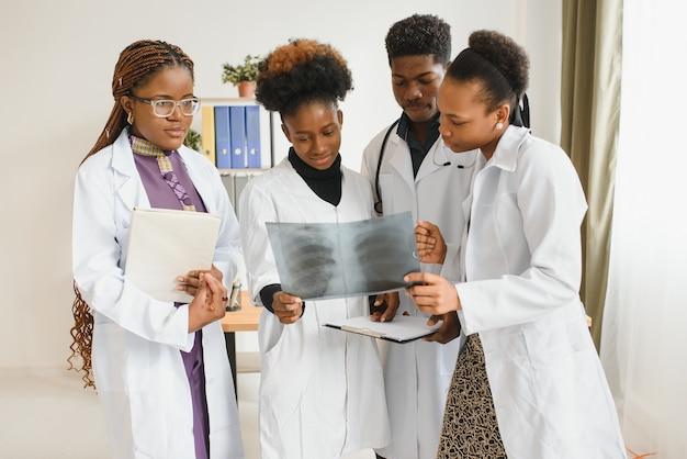 Grupa lekarzy w biurze z prześwietleniem pacjenta
