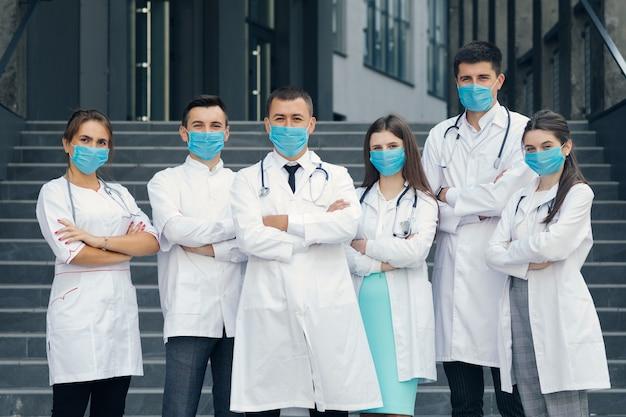 Grupa lekarzy z maskami na twarz, patrząc na kamery. lekarze specjalizujący się w pracy zespołowej. wirus corona i koncepcja opieki zdrowotnej.
