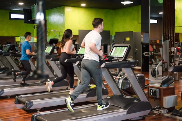 Grupa ludzi biegających na bieżniach w nowoczesnej siłowni sportowej.