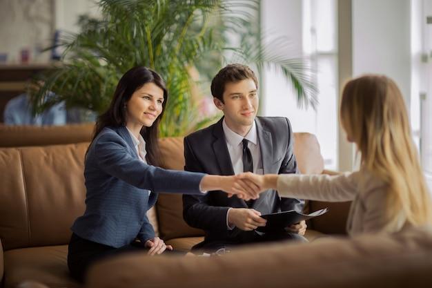 Grupa ludzi biznesu gratulująca kolegom uścisku dłoni po podpisaniu umowy