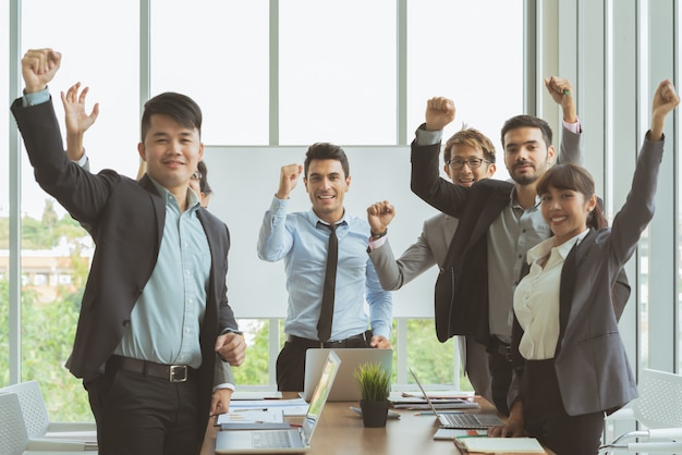 Grupa ludzi biznesu kolega spotkanie stały i ręce podniesione razem gotowy do pracy na sukces