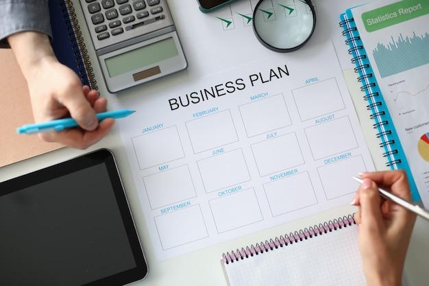 Grupa ludzi biznesu, którzy odbywają spotkanie robocze przy stole z papierowymi dokumentami omawiającymi roczny biznesplan