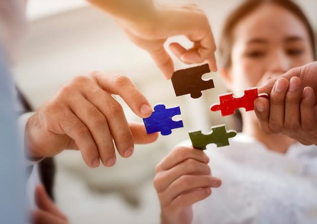 Grupa ludzi biznesu montuje puzzle i reprezentuje wsparcie zespołu i pomoc razem.