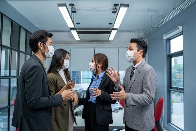 Grupa ludzi biznesu noszących maskę w celu ochrony covid-19 ma spotkanie i rozmowę w biurze.