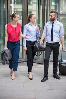 Grupa ludzi biznesu opuszczających budynek biurowy