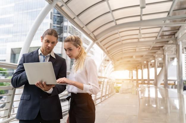 Grupa ludzi biznesu pracujących i omawiających coś pozytywnego ze swoim dojrzałym kolegą i korzystających z laptopa na świeżym powietrzu w stolicy