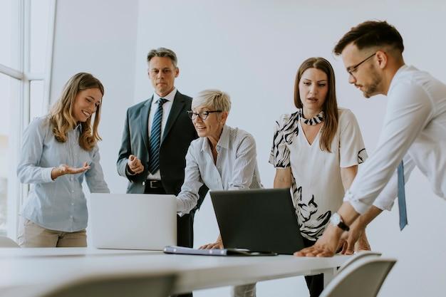 Grupa ludzi biznesu pracujących razem i przygotowujących nowy projekt na spotkaniu w biurze