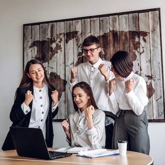 Grupa ludzi biznesu pracujących w biurze na wspólnym spotkaniu robi zwycięski gest