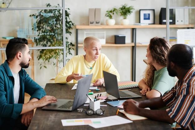 Grupa ludzi biznesu siedząca przy stole i dyskutująca o pracy razem ze swoim liderem podczas spotkania w biurze