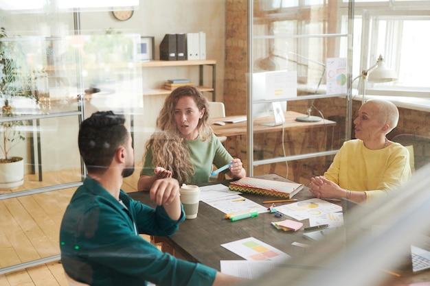 Grupa ludzi biznesu siedząca przy stole i dyskutująca w zespole podczas spotkania w biurze za szybą
