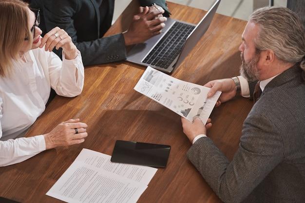 Grupa ludzi biznesu siedząca przy stole i wspólnie omawiająca dokumenty w zespole podczas spotkania w biurze