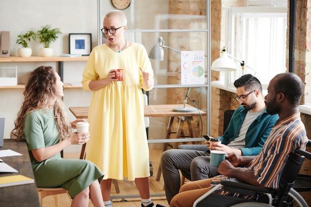 Grupa ludzi biznesu siedzących w kręgu i planujących wspólną pracę w zespole podczas spotkania w biurze