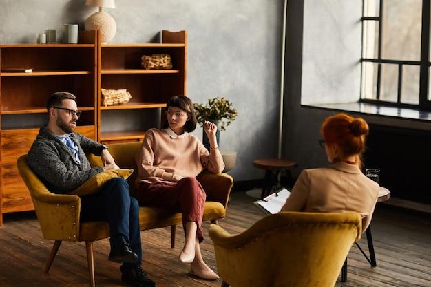 Grupa ludzi biznesu siedzi na fotelach i wspólnie omawia plany na przyszłość podczas spotkania w biurze