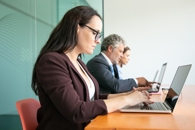 Grupa ludzi biznesu siedzi w kolejce i przy użyciu komputerów w biurze. pracownicy w różnym wieku piszący na klawiaturach laptopów.