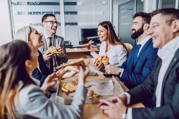 Grupa ludzi biznesu siedzi w sali konferencyjnej, rozmawiając, śmiejąc się i jedząc pizzę na obiad.