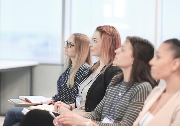 Grupa ludzi biznesu słuchająca wykładu na seminarium biznesowym