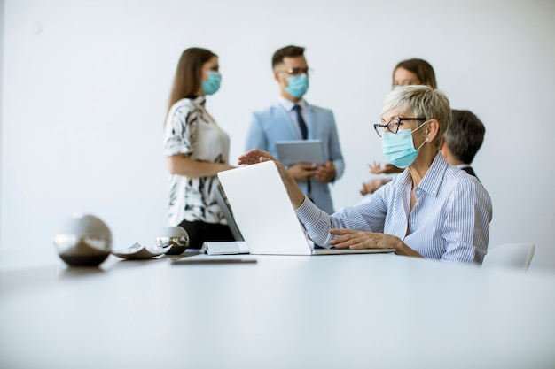 Grupa ludzi biznesu spotyka się i pracuje w biurze i noszą maski chroniące przed wirusem koronowym