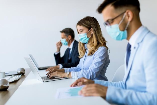 Grupa ludzi biznesu spotyka się i pracuje w biurze i noszą maski jako ochronę przed wirusem koronowym