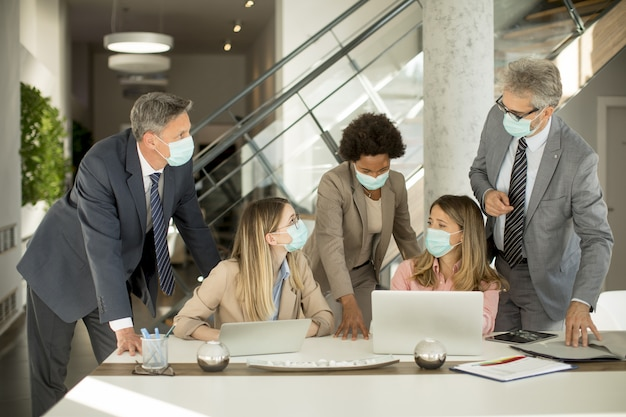 Grupa ludzi biznesu spotyka się i pracuje w biurze i noszą maski w celu ochrony przed koronawirusem