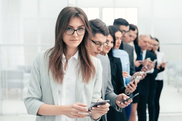 Grupa ludzi biznesu stojących w rzędzie ze smartfonów