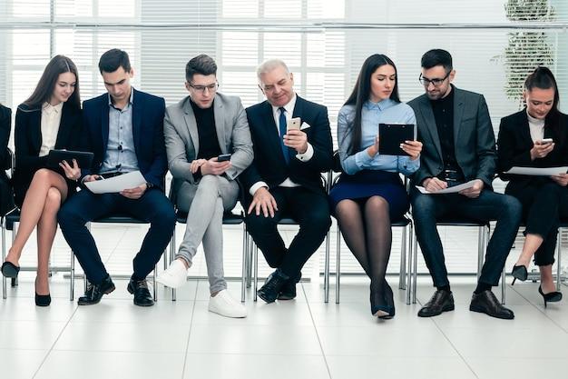 Grupa ludzi biznesu używa swoich gadżetów przed rozpoczęciem spotkania biznesowego. zdjęcie z kopią miejsca