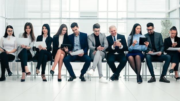 Grupa ludzi biznesu używa swoich gadżetów przed rozpoczęciem spotkania biznesowego.