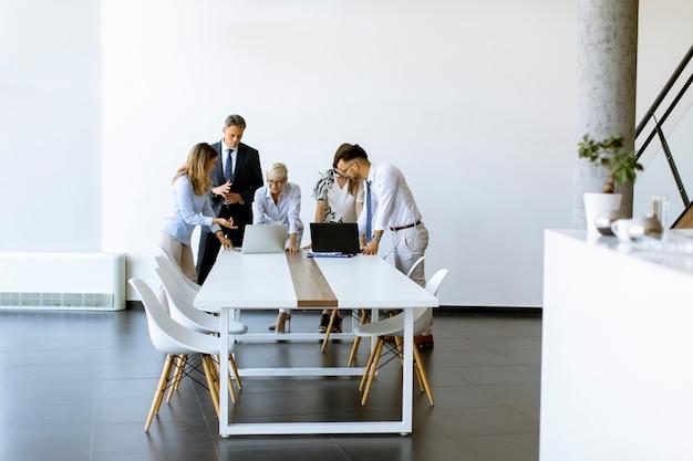 Grupa ludzi biznesu z młodymi dorosłymi i starszym koleżanką na spotkaniu w nowoczesnym, jasnym wnętrzu biurowym