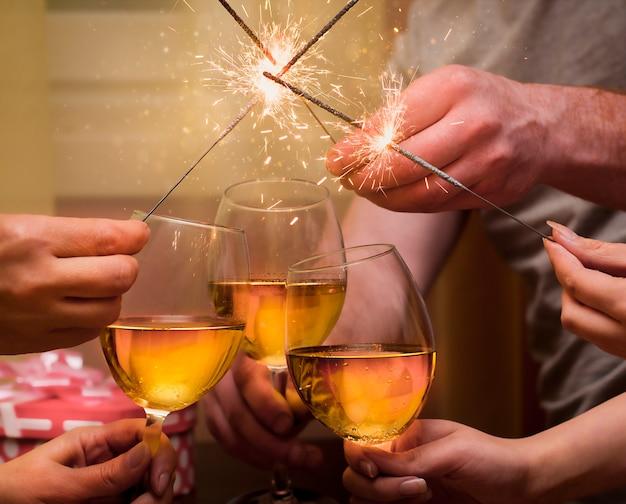 Grupa ludzi brzęka kieliszkami szampana i lekkimi zimnymi ogniami
