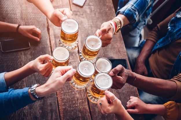 Grupa ludzi cieszących się i wznoszących toast za piwo w browarze - koncepcja przyjaźni z młodymi ludźmi, zabawy razem