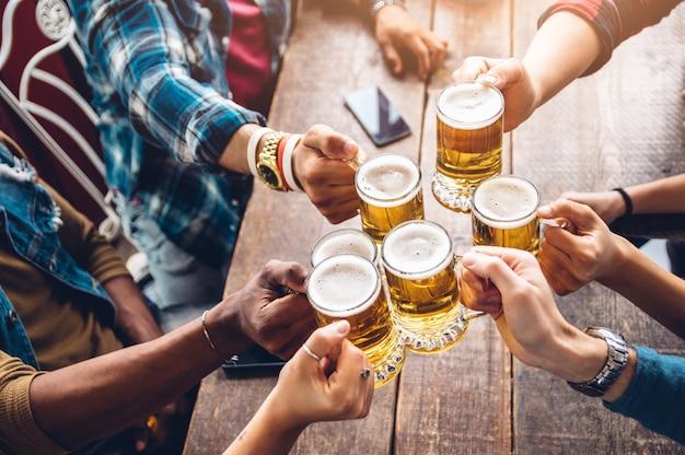 Grupa ludzi cieszących się i wznoszących toast za piwo w pubie w browarze - koncepcja przyjaźni z młodymi ludźmi, zabawy razem