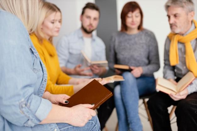 Grupa ludzi czytająca książki na sesji terapeutycznej