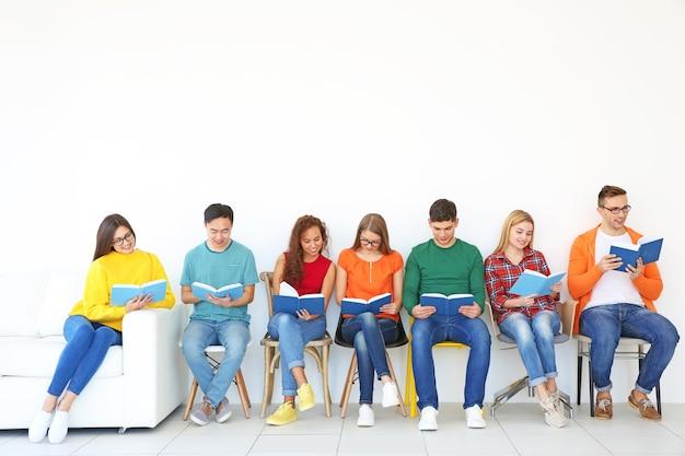 Grupa ludzi czytających książki, siedząc w pobliżu lekkiej ściany