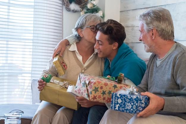 Grupa ludzi, dziadkowie i młody wnuk świętują noc bożego narodzenia w domu z prezentami i prezentami
