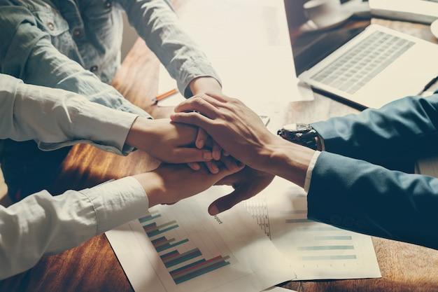 Grupa ludzi hand together łączenie dla zbudowanego zespołu w biurze