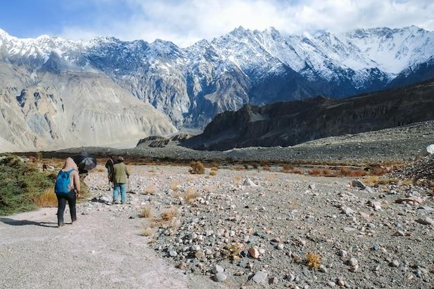 Grupa ludzi idących szlakiem trekkingowym w passu.