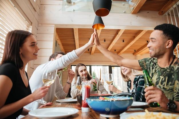 Grupa ludzi je obiad i daje piątkę