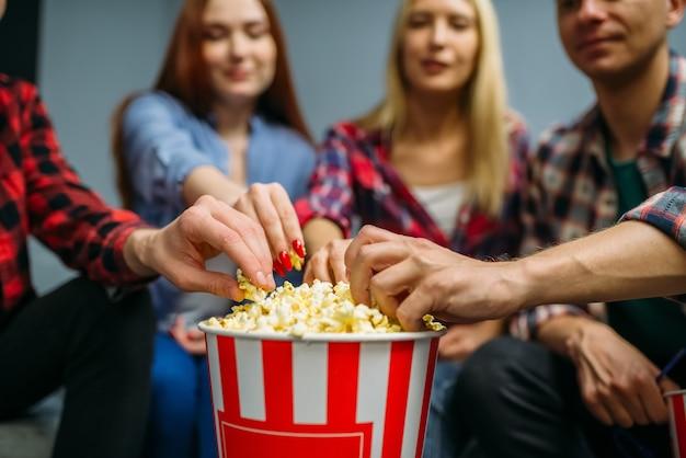 Grupa ludzi jedzących popcorn i bawiących się w sali kinowej przed seansem. młodzieży płci męskiej i żeńskiej siedzi na kanapie w kinie