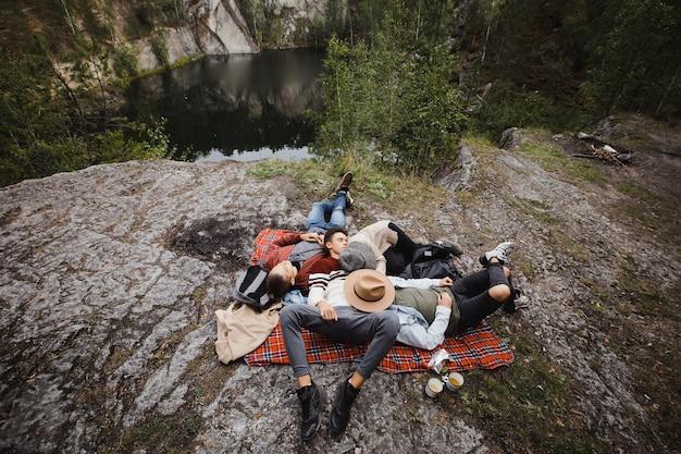 Grupa ludzi leżących razem na kocu