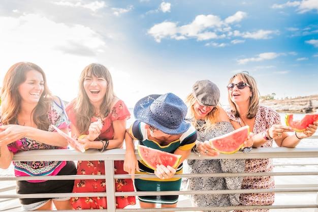 Grupa ludzi młodych kaukaskich kobiet razem bawiących się w letnie wakacje razem w przyjaźni jedzący czerwony arbuz i śmiejący się dużo - szczęśliwe kobiety na świeżym powietrzu