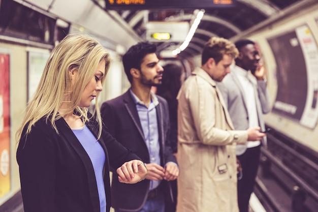 Grupa ludzi na platformie przy dworcem